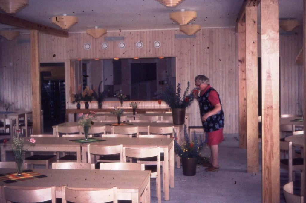 Ekegårdens legendariska husmor Aina dekorerar i den helt nybyggda matsalen. Inget golv ännu så det får duga med trasmattor. Nu är det dags att inviga!